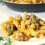 A white plate with butternut squash pasta and sausage and a pan with more pasta in the background