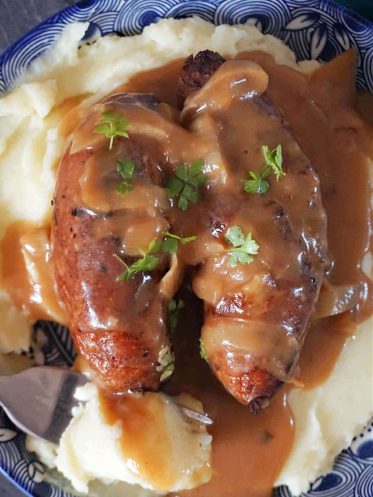 Close-up shot of 2 sausages in gravy over a bed of mash