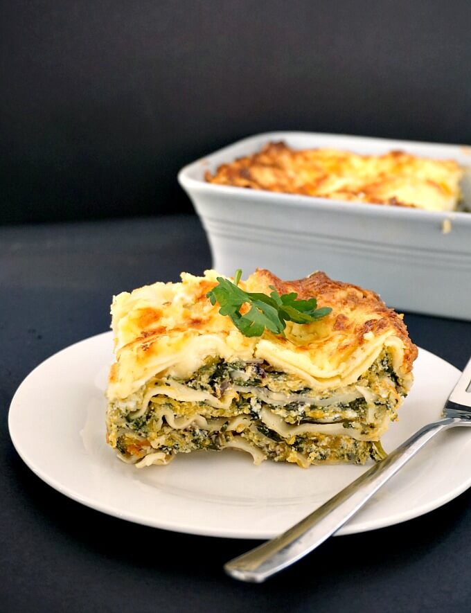 Butternut squash spinach lasagna on a white plate with a fork next to it and a lasagna dish in the background