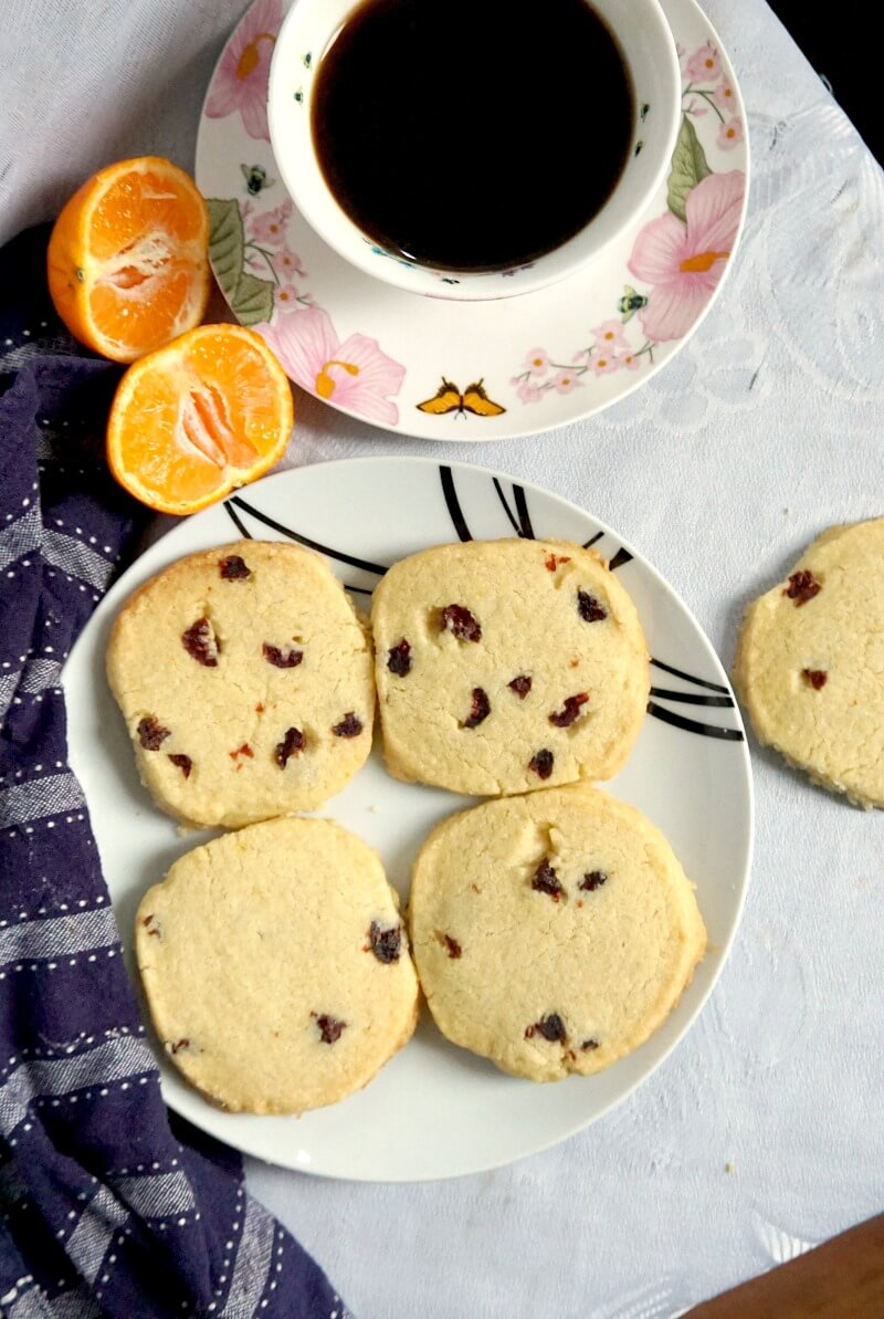 Overhead shot of a white plate with 4 cranberry orange shortbread cookies