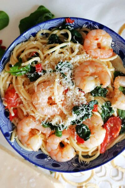 Overhead shoot of a blue plate with spaghetti tossed with prawns, spinach and tomatoes