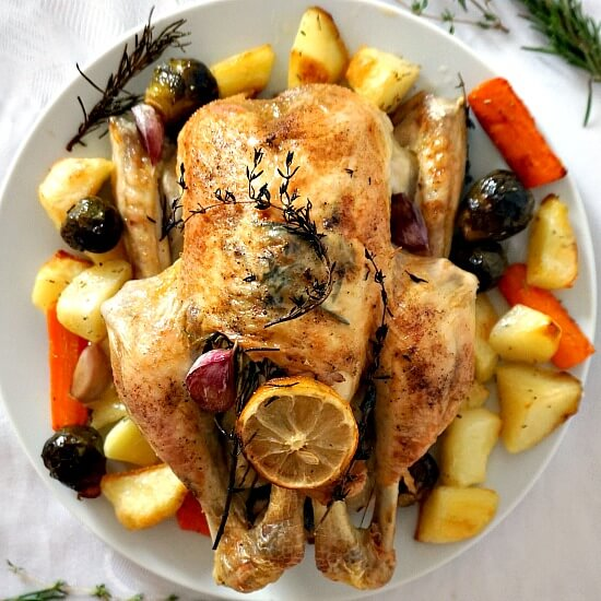 Overhead view of a whole roasted chicken with vegetables on a white plate