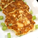 2 Chicken Fritters on a white plate with chopped spring onions around