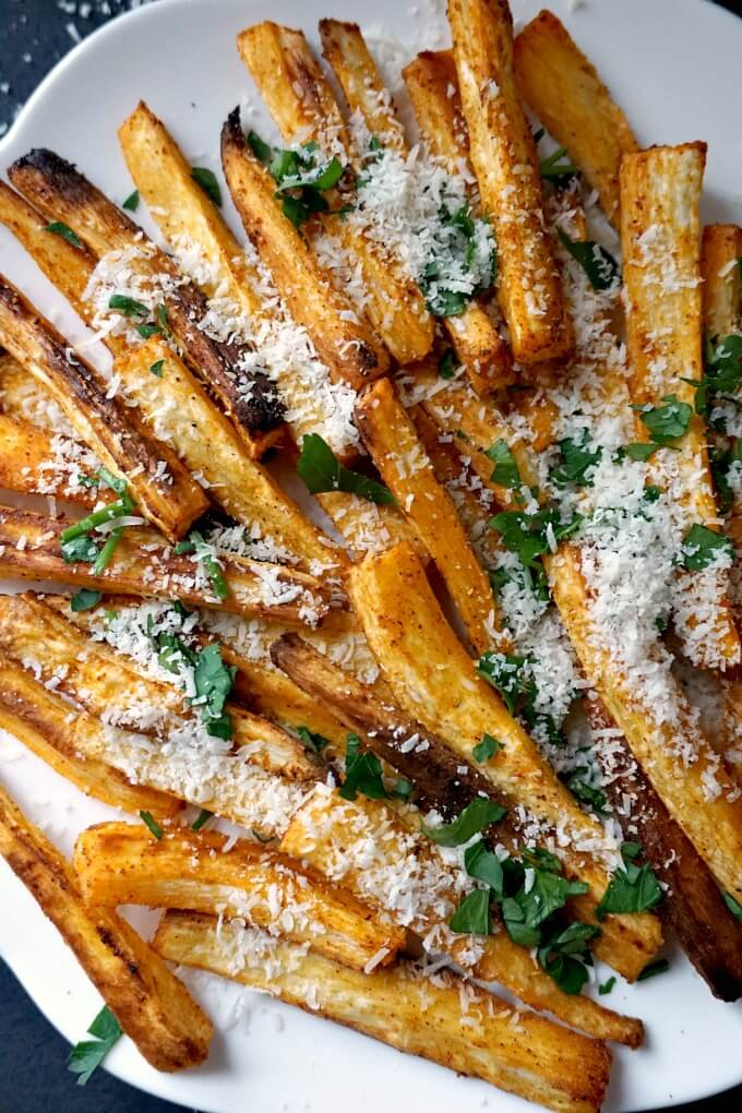 Close-up shot of baked parsnip fries with parmesan and parsley