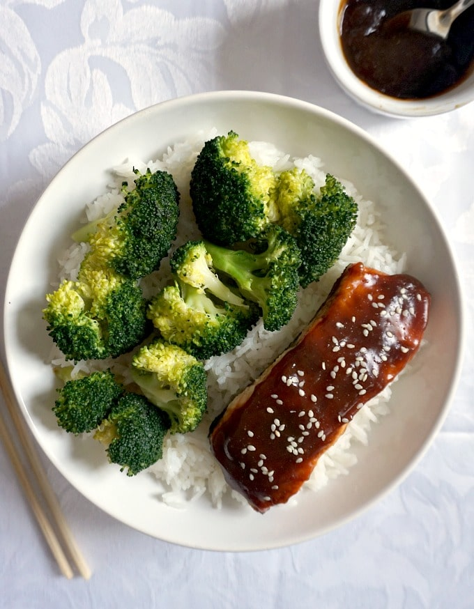 Overhead shot of a white plate with baked teriyaki salmon and broccoli on a bed of rice