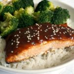 Baked teriyai salmon with sesame seeds and broccoli on a bed of rice.