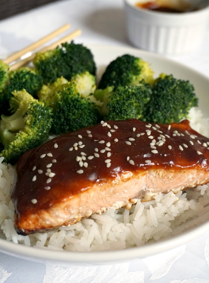 A white plate with teriyaki salmon, with borccoli florets over a bed of rice