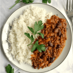 Overhead shot of a white plate with rice and homemade chili with rice and a sprig of fresh parsley