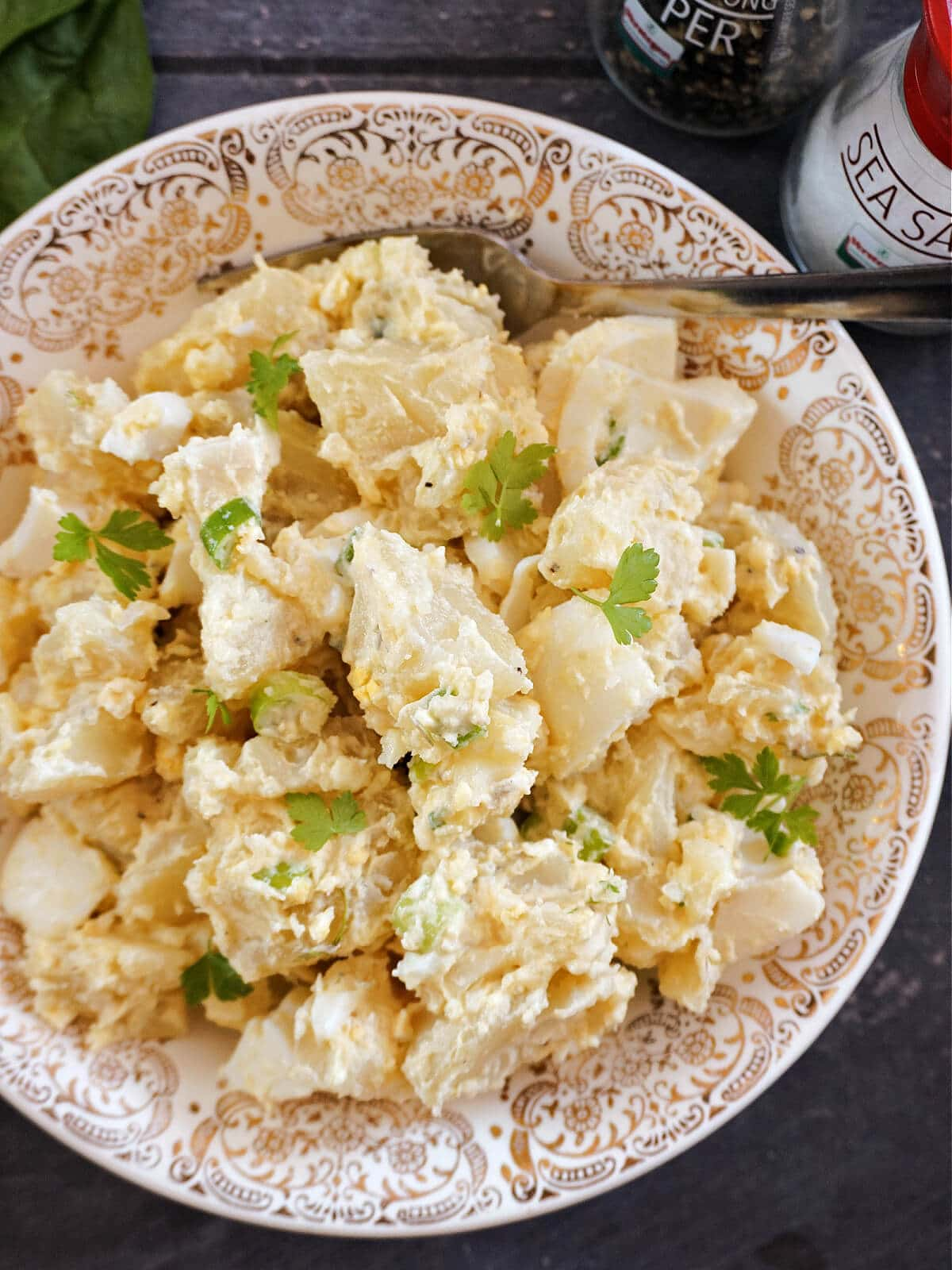 A plate with potato salad garnished with fresh parsley