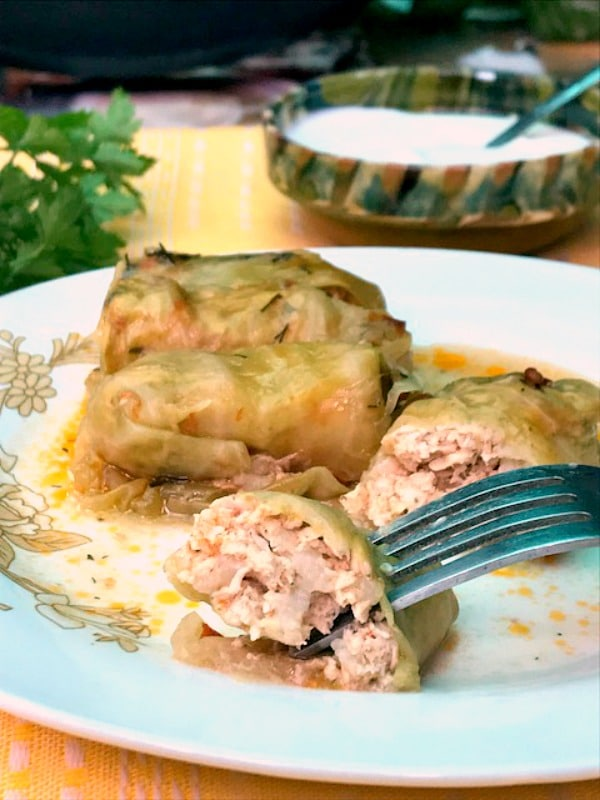 A white plate with stuffed cabbage rolls