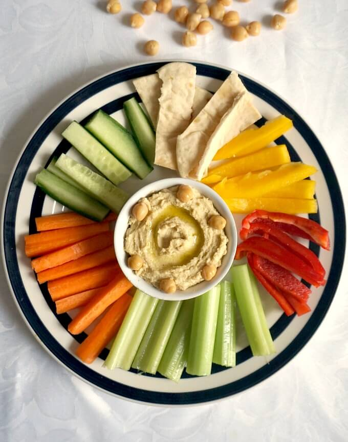 Overhead shot of a platter with spicy hummus in a hite bowl surrounded by vegetables and flatbread strips
