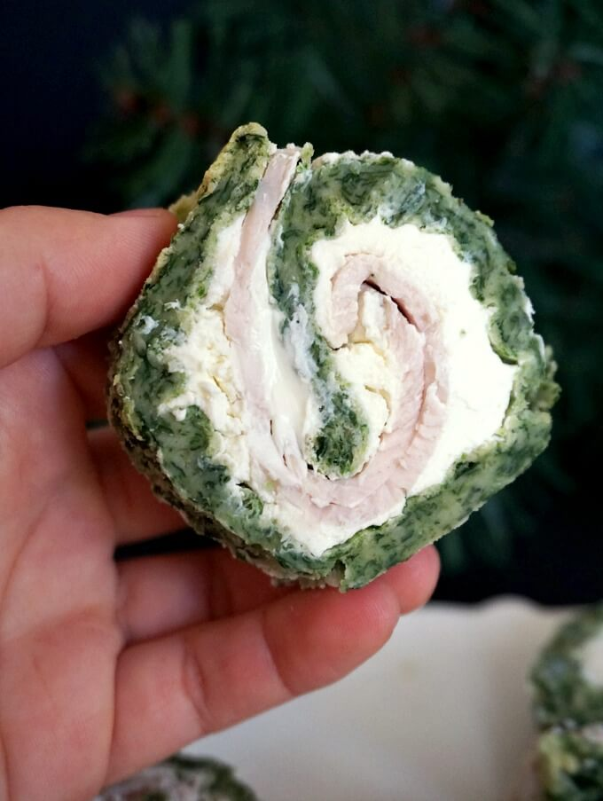 Hand holding a spinach roll up with ham and cream cheese