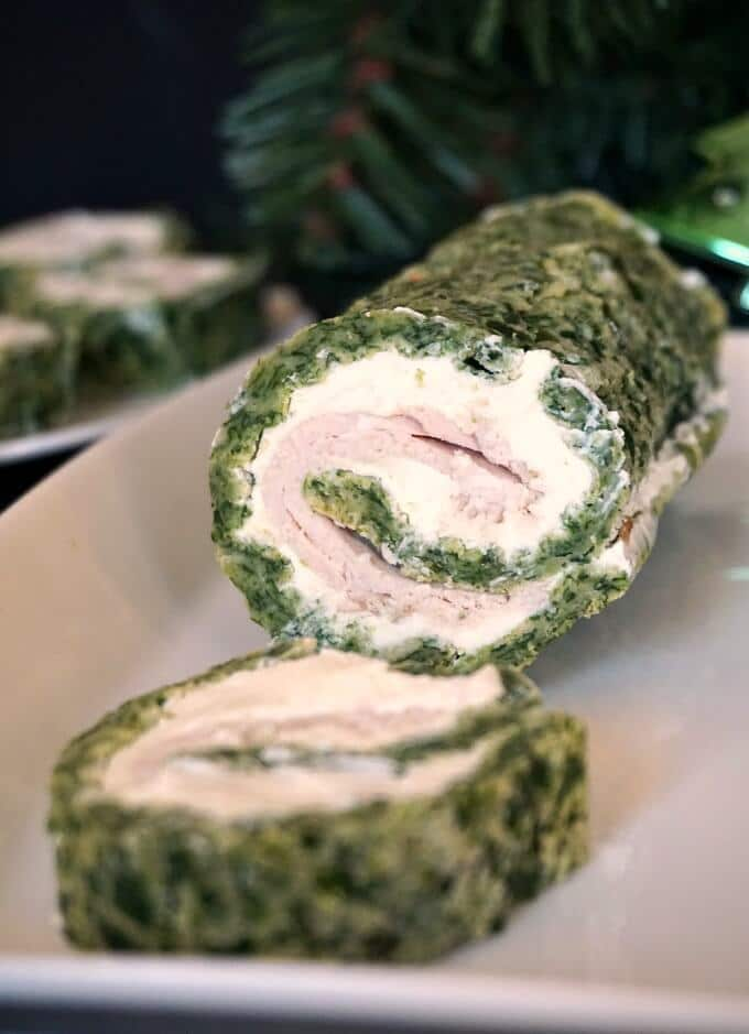 A white plate with a spinach roll and a sliced roll up