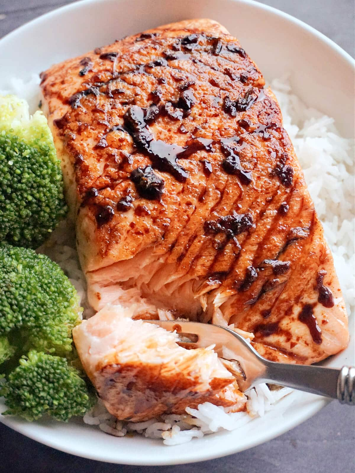 Close-up shot of a salmon filler over a bed of rice and 2 broccoli florets next to it