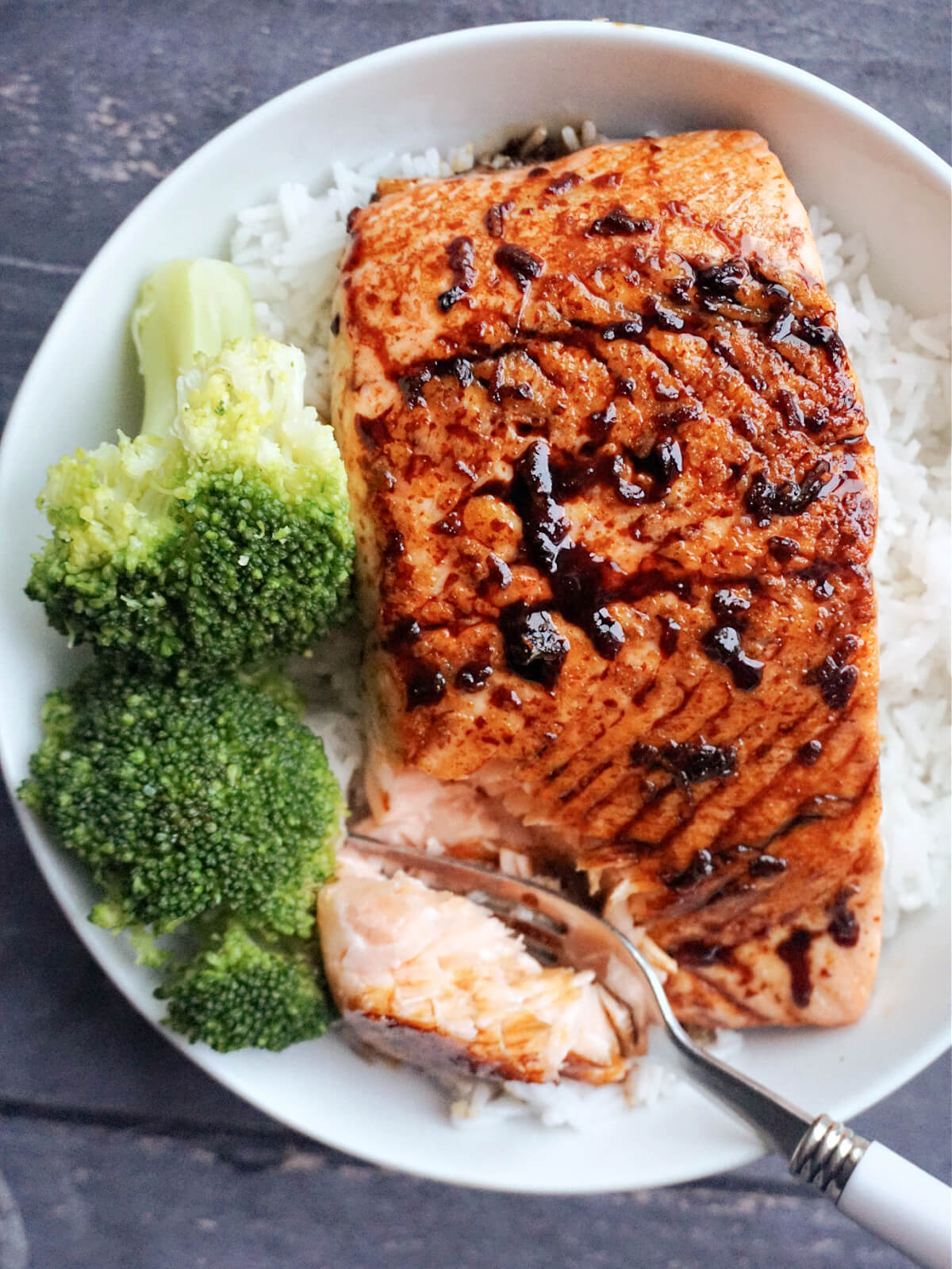 A fillet of teriyaki salmon over a bed of rice and 2 broccoli florets