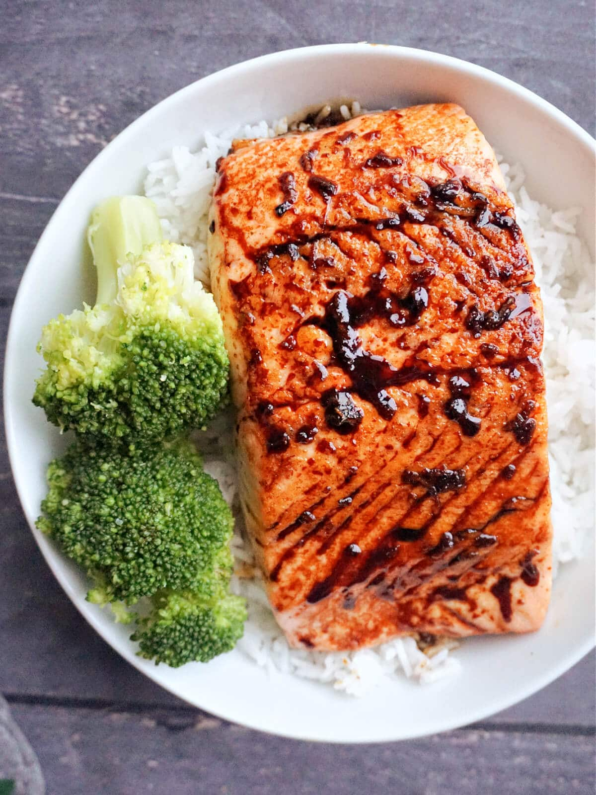 Overhead shot of a salmon fillet over a bed of rice and 2 broccoli florets