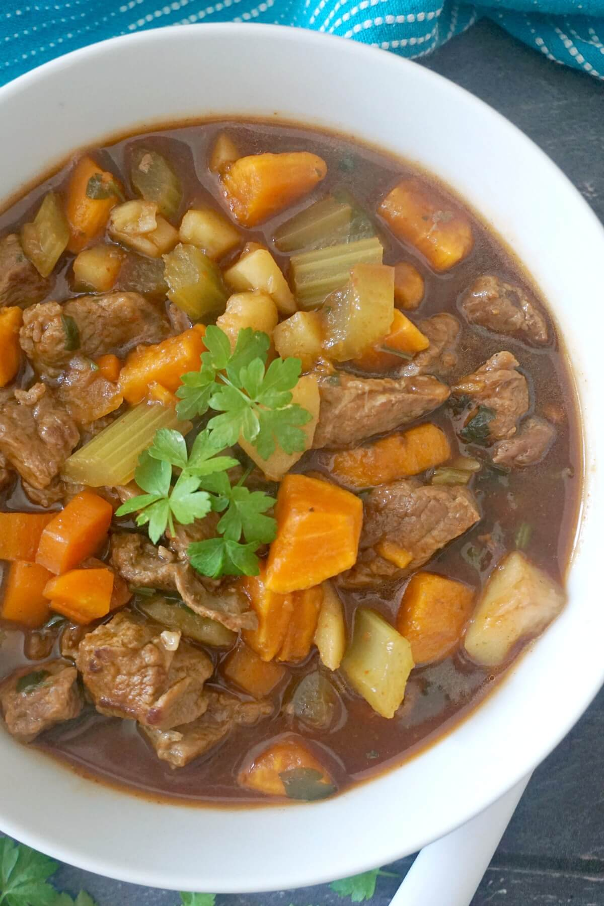A white bowl with beef and sweet potato stew
