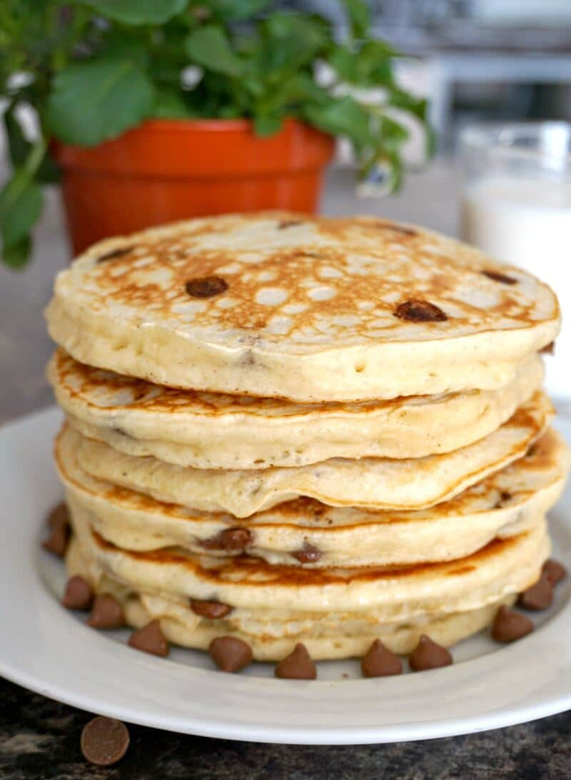 A stack of 5 pancakes on a white plate