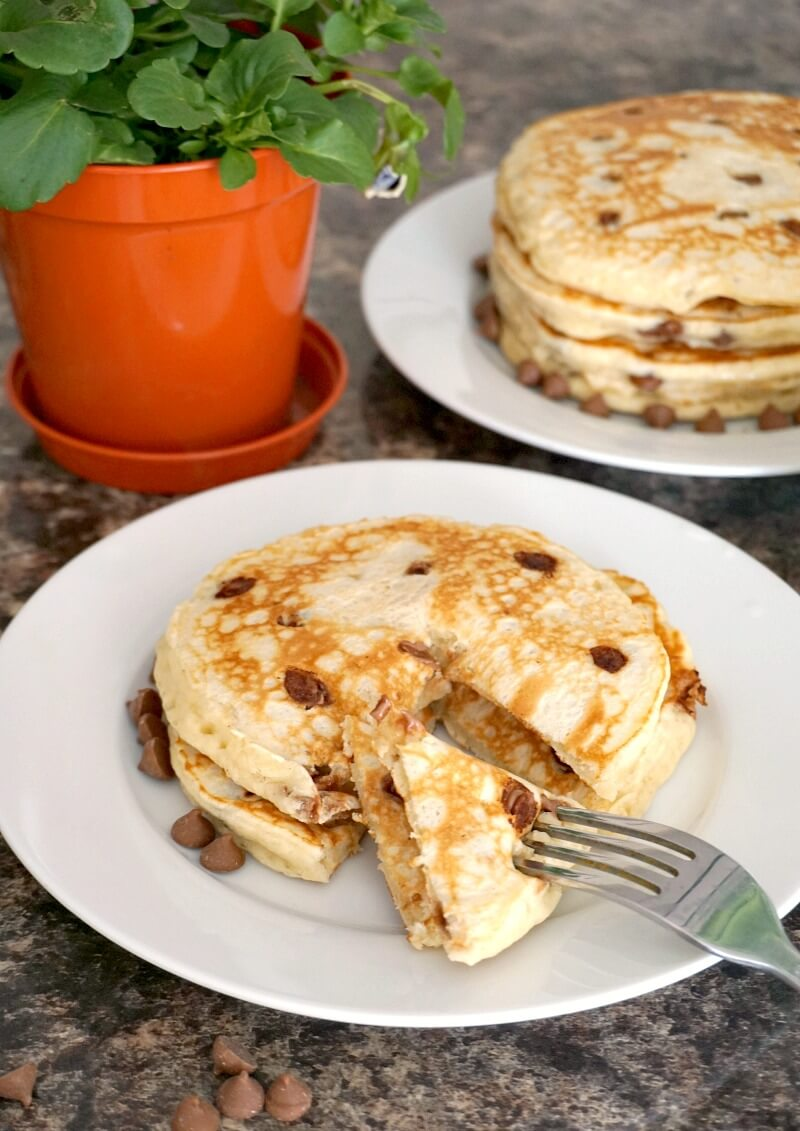 A white plate with choc chip pancakes and another plate in the backgroudn