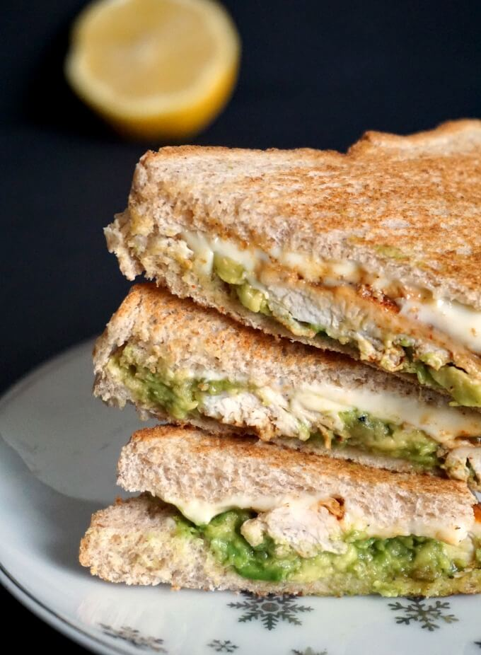 A stack of grilled chicken sandwiched with avocado and half a lemon in the background