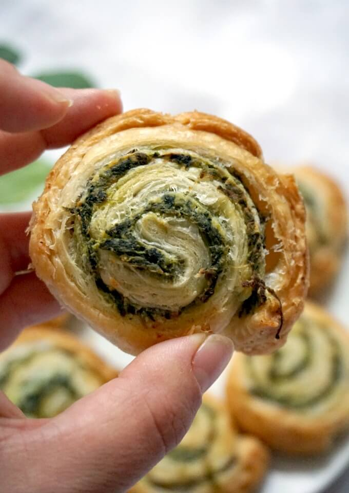 A spinach pinwheels with other pinwheels in the background