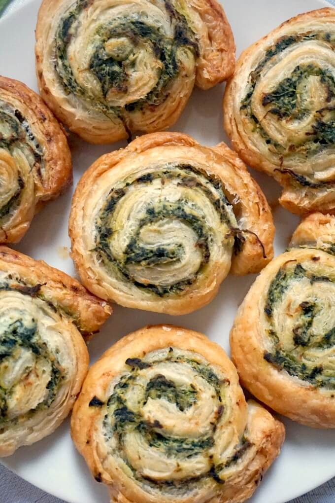 Close-up shot of 7 spinach pinwheels on a white plate