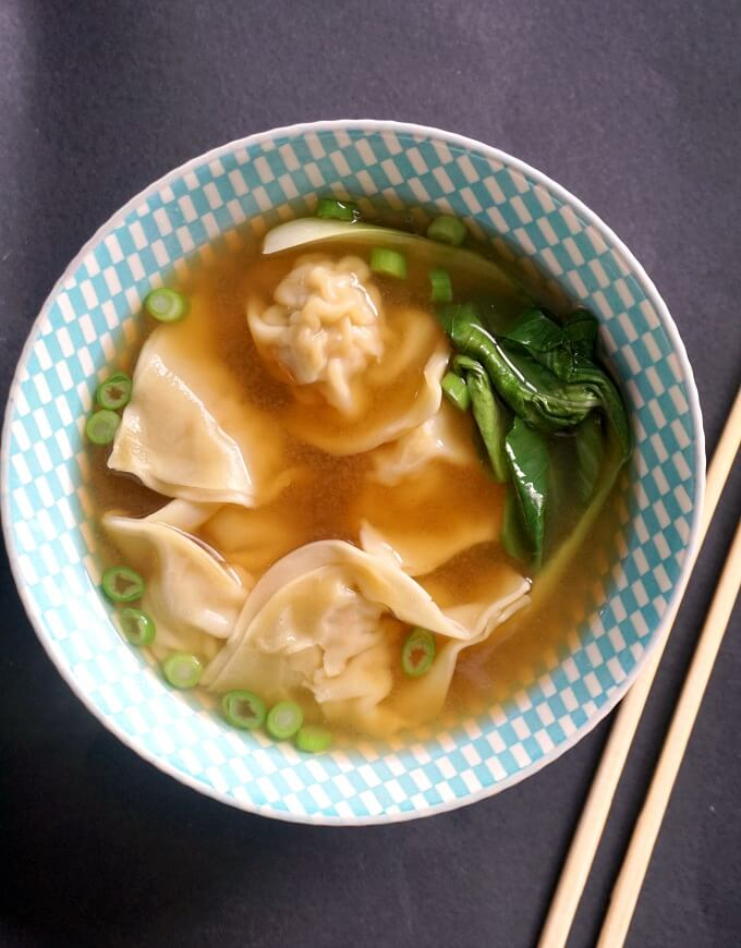 Overhead shot of a bowl of wonton soup with chopsticks on the side
