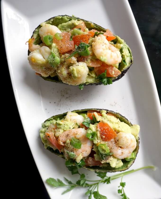 Overhead shot of a white plate with 2 avocado skins stuffed with avocado shrimp salad