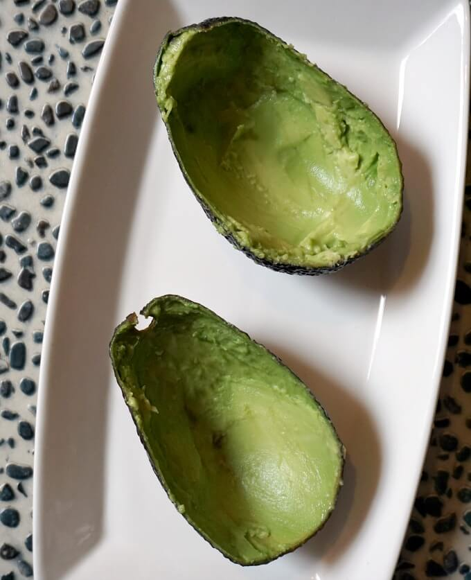 2 avocado skins on a white plate