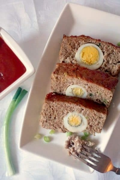 Overhead shot of a rectangle white plate with 3 slices of moist turkey meatloaf stuffed with hard-boiled eggs, a small cup of ketchup and a spring onion on the side