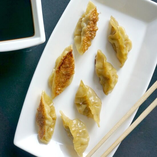 Overhead shot of a white plate with 8 pan-fried chinese dumplings