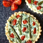 Overview shot of a Tomato, Spinach and Asparagus Tartlets with Ricotta, a tomato cut in 4 and a bit of another tartlet