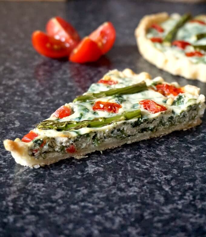 A slice of asparagus tartlet with a tomato cut in 4 in the backgorund