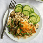Overhead shoot of a white plate with baked chicken with rice and mushrooms and a cucumber salad on the side. Another pan with baked chicken with rice and mushrooms in the background