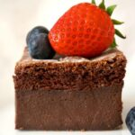 Close-up shot of a slice of chocolate magic cake tiopped with berries