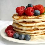 A stack of egg-free pancakes topped with berries