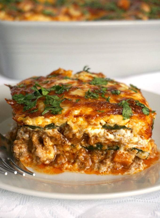 A white plate with a slice of high protein low carb zuccini lasagna and a fork on the side