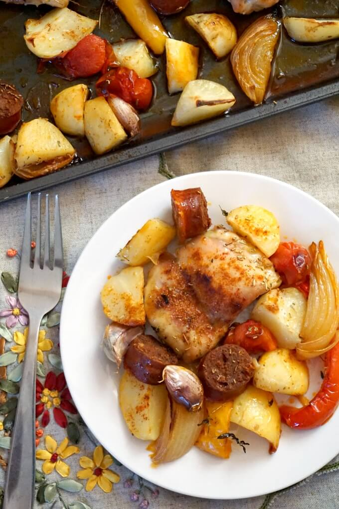 Overhead view of a white plate with vegetables, chicken with chorizo and a fork next to it