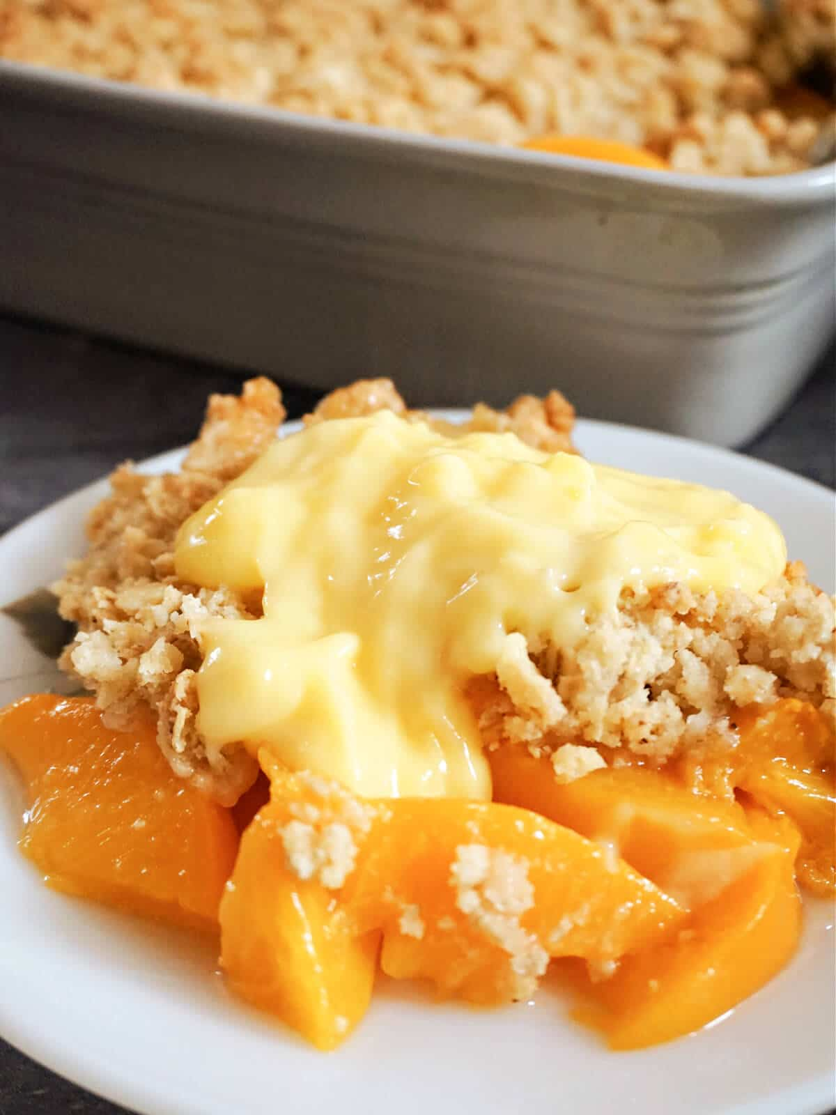 A white plate with peach crumble and a dish with more crumble in the background