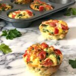 2 egg muffin cups on a table with a muffin tin with other 4 muffin cups in the background