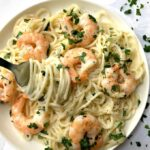 Overhead shoot of a white plate with shrimp alfredo pasta