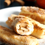 3 Apple Pie French Toast Roll-Ups and half a roll on a white plate