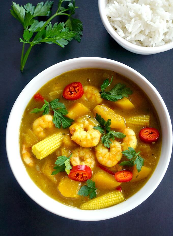 Overhead shoot of a bowl of coconut shrimp curry, a small bowl of rice and a sprig of fresh parsley