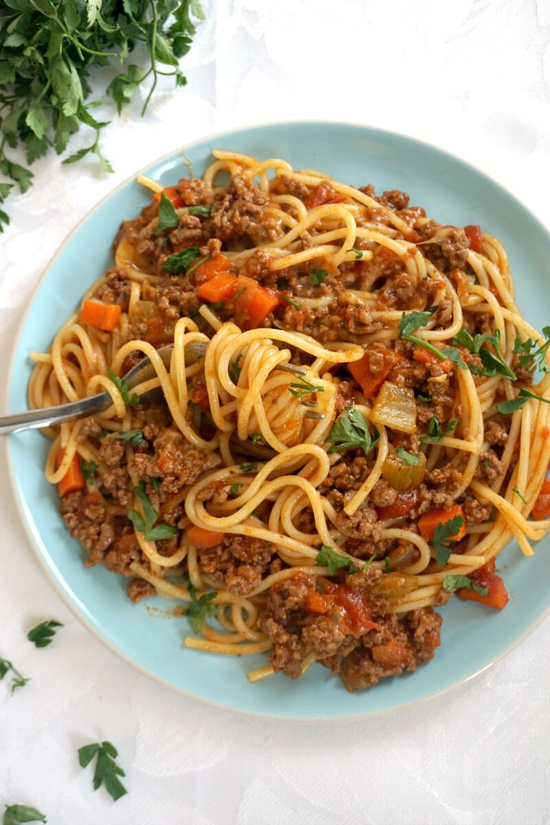 Overhead shoot of a blue plate with spaghetti bolognese