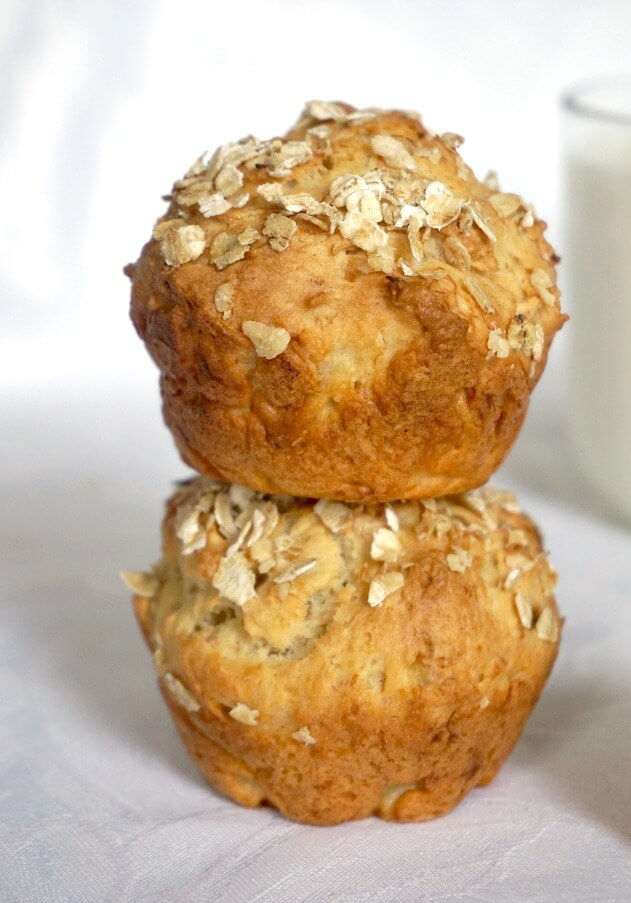 A stack of 2 banana muffins with a glass of milk in the background