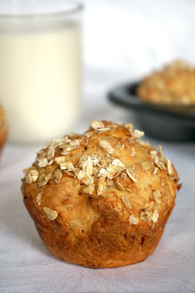 A banana muffin with a tray of muffins and a glass of milk in the background