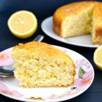 A slice of lemon drizzle cake on a plate with more cake in the background