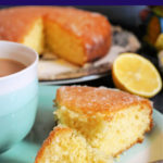 A slice of lemon drizzle cake on a light blue plate with half a lemon and more cake in the background