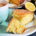 A slice of lemon drizzle cake with more cake in the background