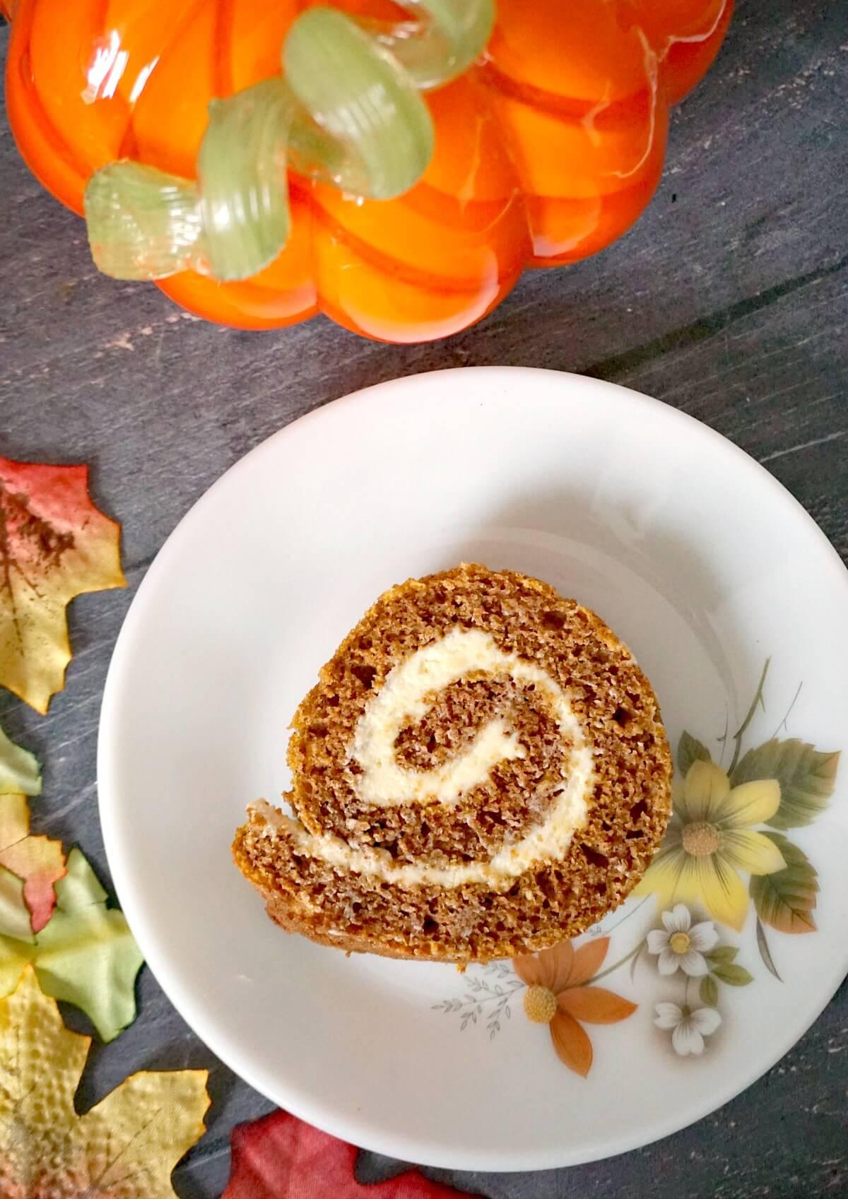 Overhead shoot of a slice of pumpkin roll on a white dessert plate